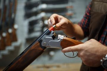 Man loads a rifle, gun shop interior on background