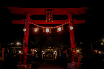 An orange torii gate leading to Mizukami Shrine lighted up at night in small Japanese city, Fujiyoshida. Torii gate is decorated with few lanterns, shining bright with light. Holly site.