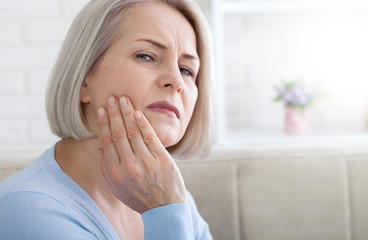 Teeth problem. Woman feeling tooth pain. Closeup of beautiful middle-aged suffering from strong toothache. Attractive female feeling painful toothache. Dental health and care concept. High resolution.