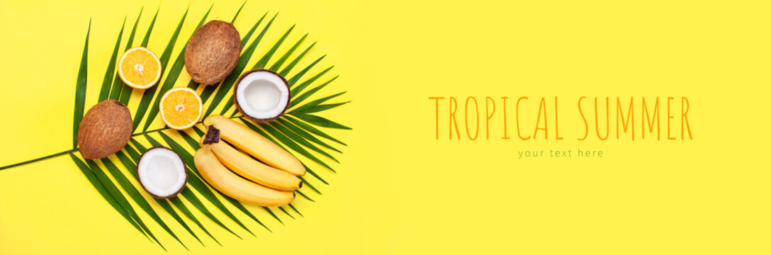 Summer tropical composition. Green tropical leaves of palm trees and monstera, coconut, orange, bananas on bright yellow background. Flat lay, top view, copy space. Creative background food, fruit