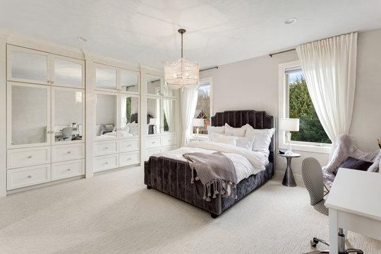 Bedroom in new luxury home with chandelier, desk, and abundant natural light