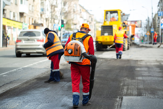 Worker with leaf-blower, cleaning out the dust for better asphalt adhesion, during tram track renewal works