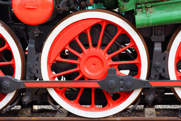 Steam locomotive, rod drive of a old locomotive. Red wheels of a steam train