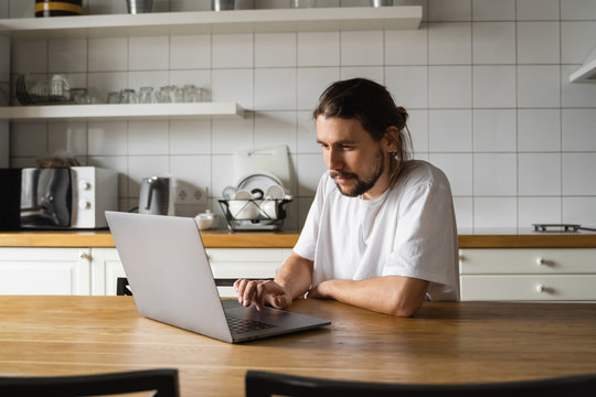 Freelancer working from home on the kitchen and using laptop. Bearded man working with a laptop and reading good news. Handsome successful self entrepreneur sitting and working at his modern home.
