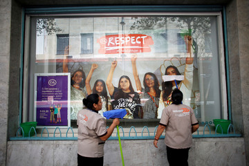 "Female workers clean the window of a shop whose employees stayed away from work during the ""Day without women"" protest, as part of the escalation of historic protests against gender violence, in Mexico City"