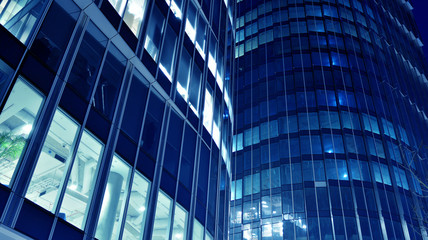Night architecture - building with glass facade.Blue color of night lights. Modern building in  business district. Concept of economics, financial. Photo of commercial office building exterior. Abstra