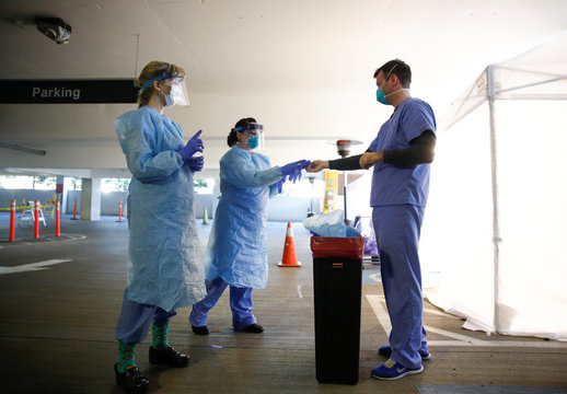 Nurses Barton and White help nurse Gates take off protective gear after interacting with a patient at a drive-through testing site for coronavirus, flu and RSV, currently by appointment for employees at UW Medical Center Northwest