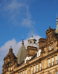 ornate stone towers and domes on the roof of leeds city market a historical building in west yorkshire england