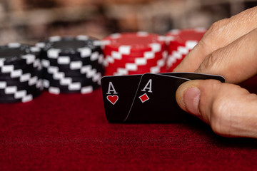 a male caucasian hand Showing a Pair of Aces in the hole, Hearts and Diamonds, on a unique deck of black faced cards with Red and Black clay poker chips in the background.  Room for Copy.