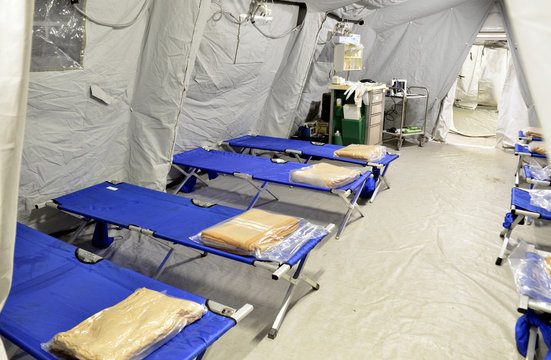 Empty hospital field tent for the first AID, a mobile medical unit of red cross for patient with Corona Virus. Interior camp room with folding camp bed  for people infected with an epidemic. Covid-19.