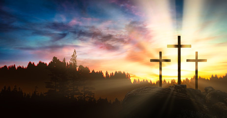three crosses on the rock at sunset