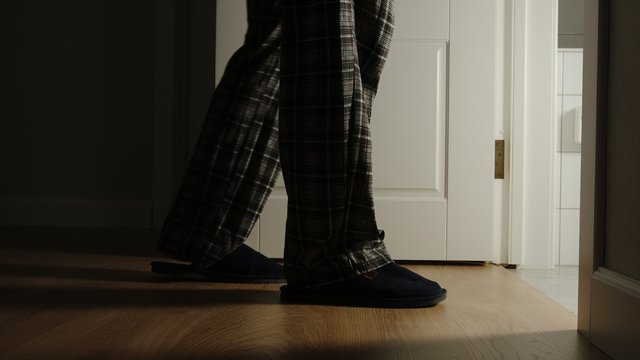 Aged man in a pajamas and slippers walks to a toilet at home in the night