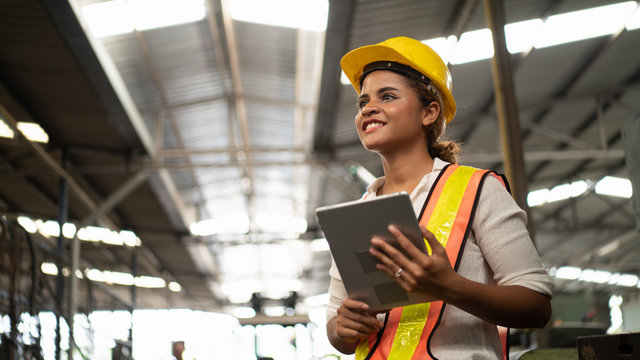 Portrait of industrial worker standing with tablet holding in her hand feeling proud and confident looking for the new opportunity, new challenge, concept manufacturing industry, Professional worker.