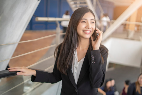 asian business woman holding a smartphone talking or calling someone on her phone looking happy and smiling while standing on an escalator wearing a suit with white t-shirt, in an urban city district.