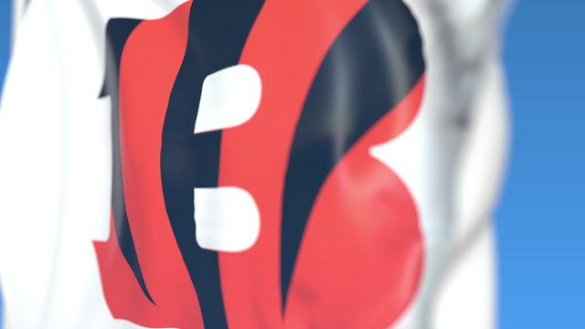 Waving flag with Cincinnati Bengals team logo, close-up. Editorial 3D rendering