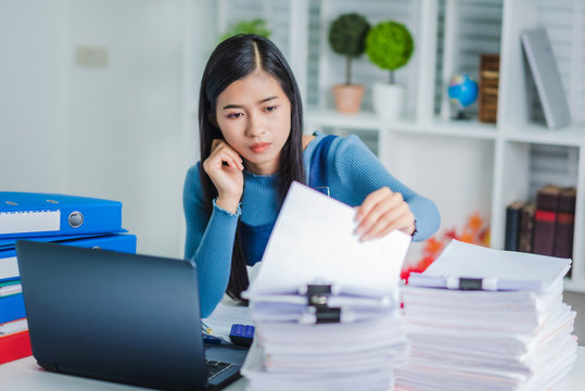 Young employee woman hands checking stack of paper files for searching unfinished document arheieve after finish busy hard working.