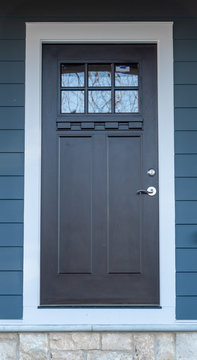 Hardwood black craftman front door on an entryway with dentil shelf and beveled glass, thich stiles and rails, white frame on a blue horizontal vinyl siding