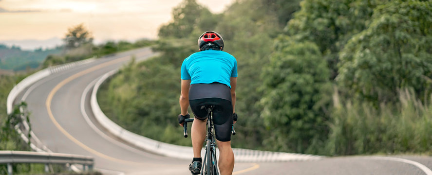 back view of a cyclist on top of a mountains winding road, riding a black bicycle down a hill, wearing bike helmet and blue cycling jersey, with grey clouds sunset sky and forest ,banner