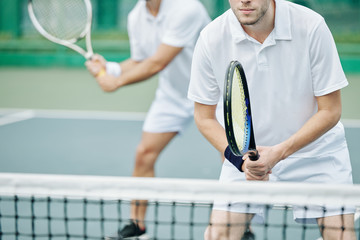 Cropped image of concentrated young tennis player standing at net and getting ready to hit the ball