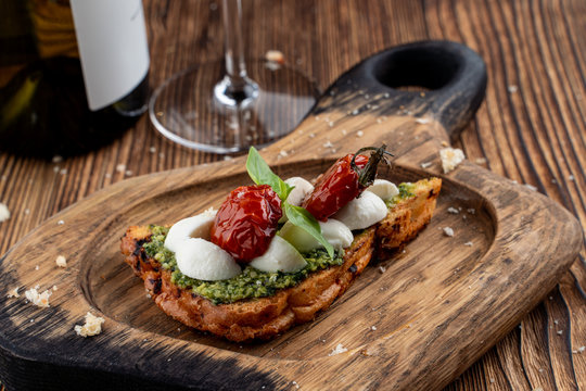Bruschetta with sun-dried cherry tomatoes, mozzarella and pesto sauce on crunchy toasted ciabatta. Served on rustic cutting board