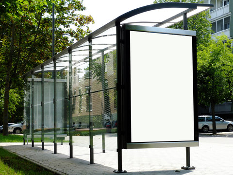 bus shelter at a bus stop. image collage of blank white glass & metal structure. urban setting with green background. safety glass design. white poster ad display. advertising concept. wooden benches.