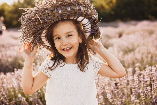 Small caucasian girl posing cheerfully in lavender field with a flower crown on head