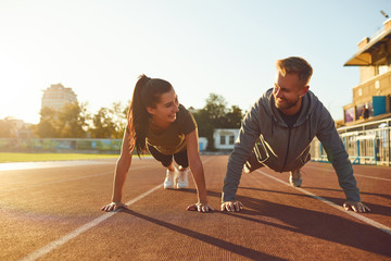 Young couple doing pushups in the stadium