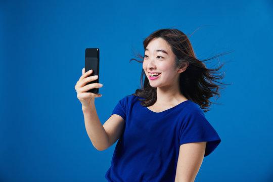 スマートフォンを持って驚く女性