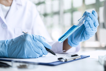 Scientist or medical in lab coat holding test tube with reagent, Laboratory glassware containing chemical liquid, Microscope, Biochemistry laboratory research