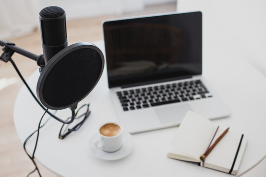 Microphone, earphones and laptop on table. Podcast