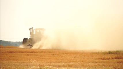 Wall Mural - A tractor with a plow plows the field after harvesting. Slow motion