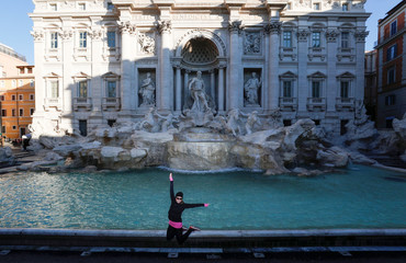 A woman jumps as she poses for a photo, next to the Trevi fountain, virtually deserted after a decree orders for the whole of Italy to be on lockdown in an unprecedented clampdown aimed at beating the coronavirus, in Rome