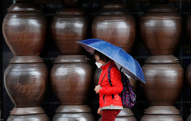 A woman, wearing a protective face mask following an outbreak of the coronavirus disease (COVID-19), walks pasts jars displayed outside a shop, in Daegu