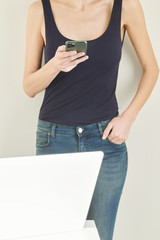 Slim girl with smartphone against gray wall