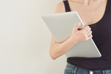 Faceless woman with laptop in hand on white background