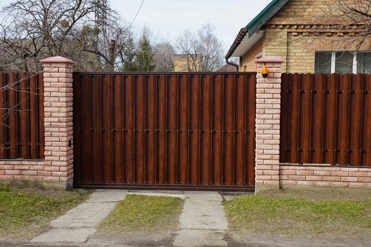 brown closed private gate and part of a fence of wooden boards and bricks on a rural street in green grass