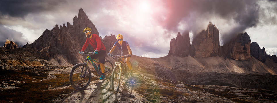 Cycling outdoor adventure in Dolomites. Cycling woman and man  on electric mountain bikes in Dolomites landscape. Couple cycling MTB enduro trail track. Outdoor sport activity.