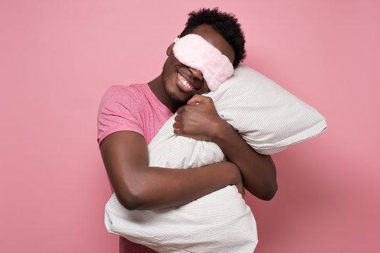Young african american black man sleeping hugging a pillow wearing sleeping mask. Studio shot on pink wall.