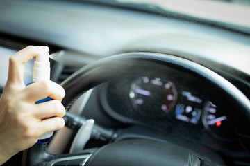 Hand of woman is spraying alcohol,disinfectant spray on steering wheel in her car,prevent infection of Covid-19 virus,contamination of germs or bacteria,wipe clean surfaces that are frequently touched