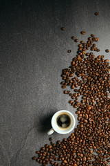 Canvas Prints Cafe Vertical top view of coffee beans and cup, on a dark ardesia table