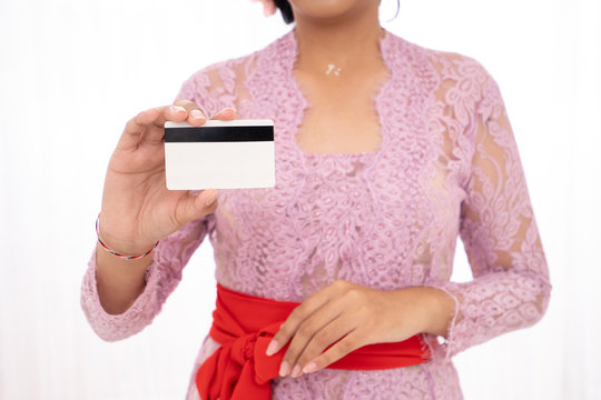 young woman wearing traditional clothing shows her credit card for shopping online
