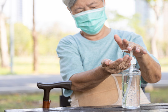 Asian elderly people wearing protective mask,using alcohol antiseptic gel,prevent infection,outbreak of Covid-19,senior woman washing hand with hand sanitizer to avoid contaminating with Coronavirus