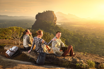 Group young tourists relaxes and watches during vacation colorful sunset on background of famous rocky plateau Lion peak, Sigiriya. Sri Lanka Fotomurales