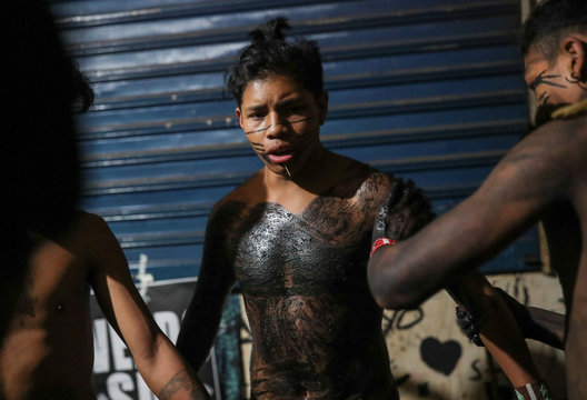 Guarani Mbya indigenous people paint their bodies black as they stay in an occupied area after an eviction order, after a protest against tree cutting and the construction of an apartment complex near Jaragua indigenous land in Sao Paulo