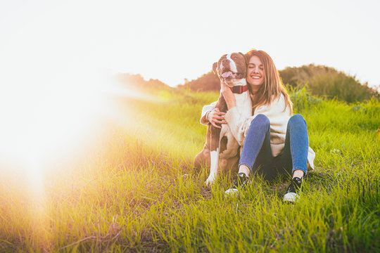 Attractive smiling woman hugging her nice dog. American Stranfrod