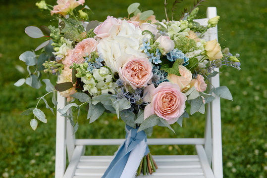 Close up of bridal bouquet of pink roses, blue flowers and greenery on white wood chair outdoors, copy space. Wedding concept