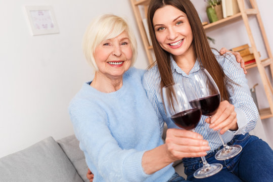Adult woman and her senior mother with wine glasses in hands
