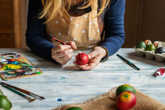 Woman painting egg and preparing for Easter holiday celebration