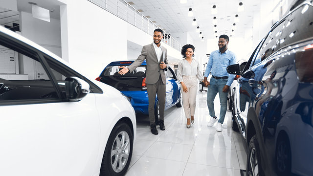 Manager Showing Luxury Automobile To Spouses In Car Dealership Center