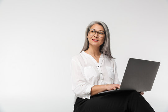 Image of adult mature woman wearing office clothes using laptop computer